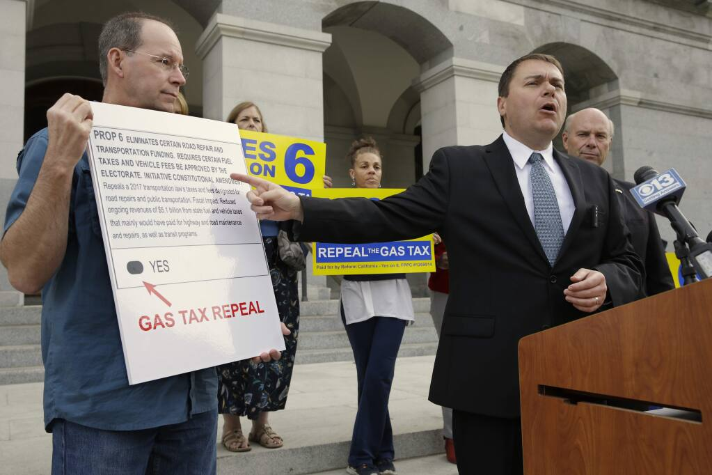 Carl DeMaio, who is leading the Proposition 6 campaign to repeal a recent gas tax increase, gestures towards a mockup of a ballot calling for voters to approve Prop. 6 on the November ballot, during a new conference Monday, Oct. 29, 2018, in Sacramento, Calif. DeMaio says that if the bid fails he'll seek to recall Democratic Attorney General Xavier Becerra saying Becerra wrote a deceiving ballot title. (AP Photo/Rich Pedroncelli)