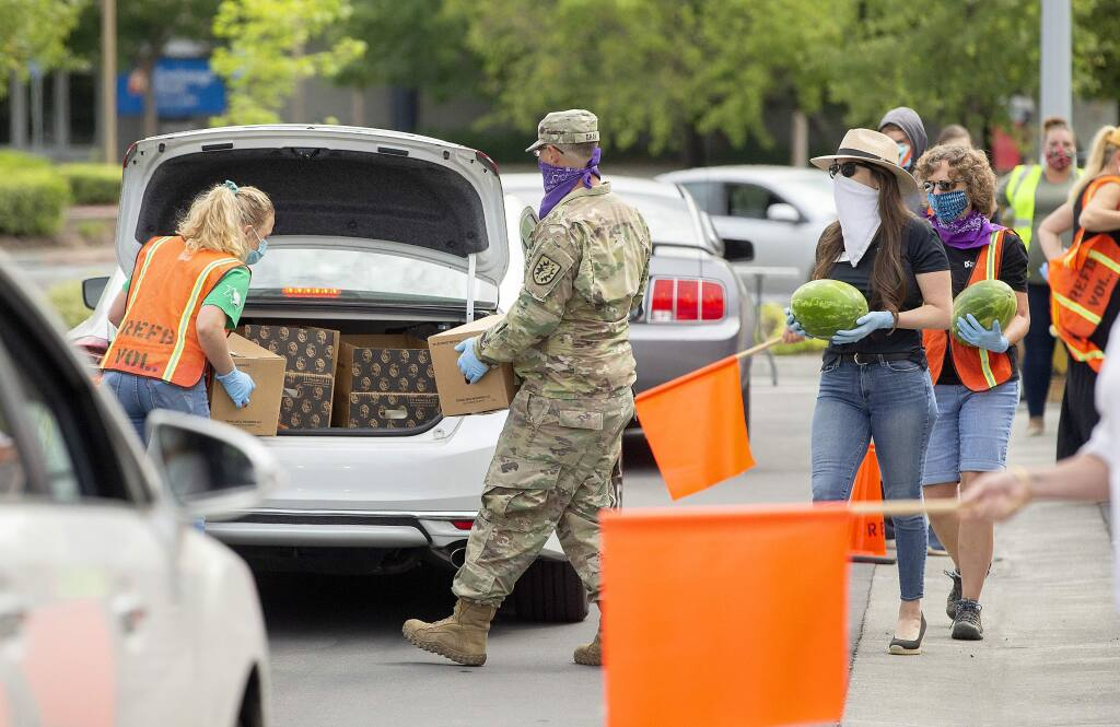 Redwood Empire Food Bank and Sonoma County Vintners Association along with the National Guard volunteer for a drive-thru food distribution to food servers, cooks, kitchen workers, bartenders and others in SoCo's pandemic-distressed hospitality industry.. (photo by John Burgess/The Press Democrat).