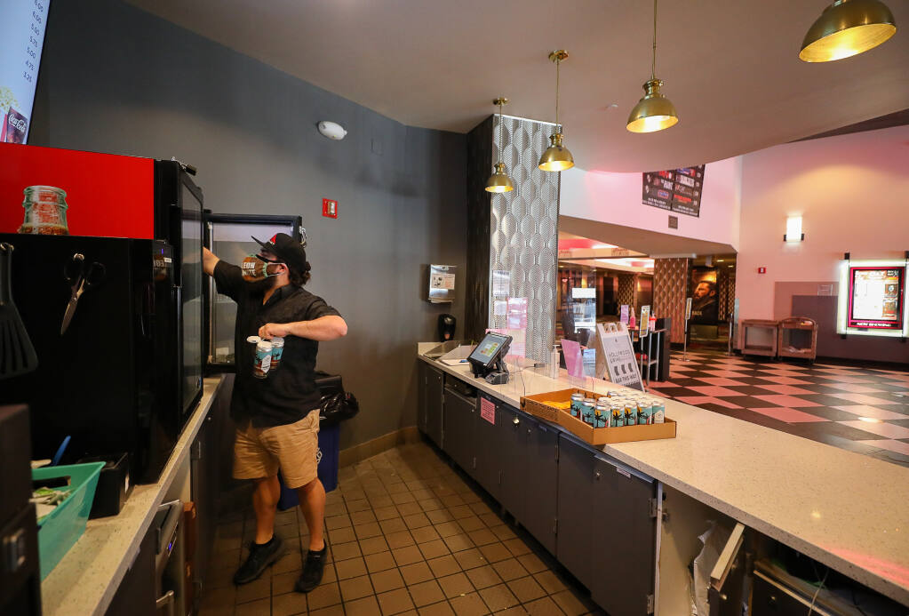 Scott Timko restocks a refrigerator at the concession stand in the Roxy Stadium 14 movie theater in Santa Rosa on Monday, March 29, 2021.  The movie theater will reopen on Wednesday, March 31.  (Christopher Chung / The Press Democrat)