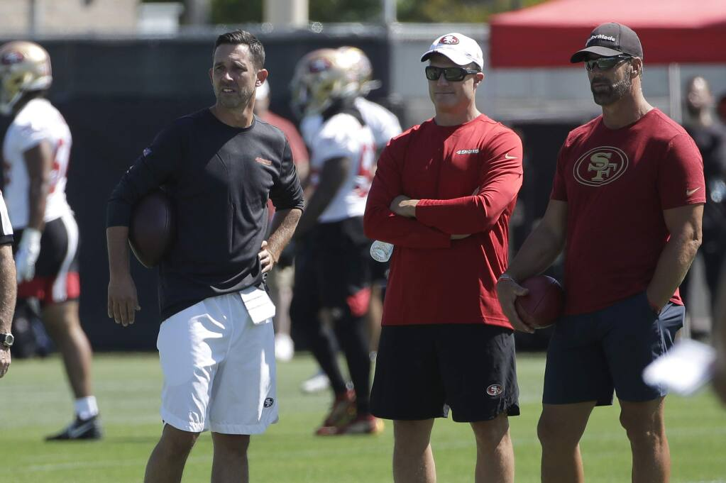San Francisco 49ers head coach Kyle Shanahan, from left, watches as players practice, with general manager John Lynch and broadcaster Tim Ryan, right, at training camp in Santa Clara, Saturday, July 27, 2019. (AP Photo/Jeff Chiu)