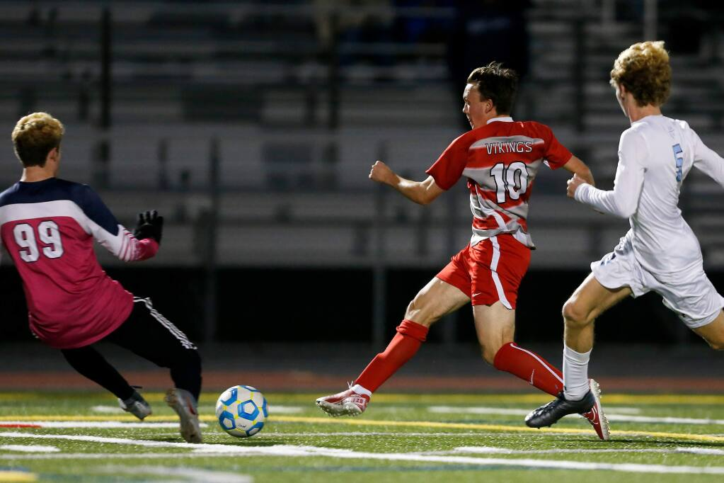 Montgomery's Zack Batchelder, second from right, kicks the ball past Bellarmine goalkeeper Ben Galdes to score during the first half of the NorCal playoffs semifinal game in Santa Rosa on Thursday, March 5, 2020. (Alvin Jornada / The Press Democrat)
