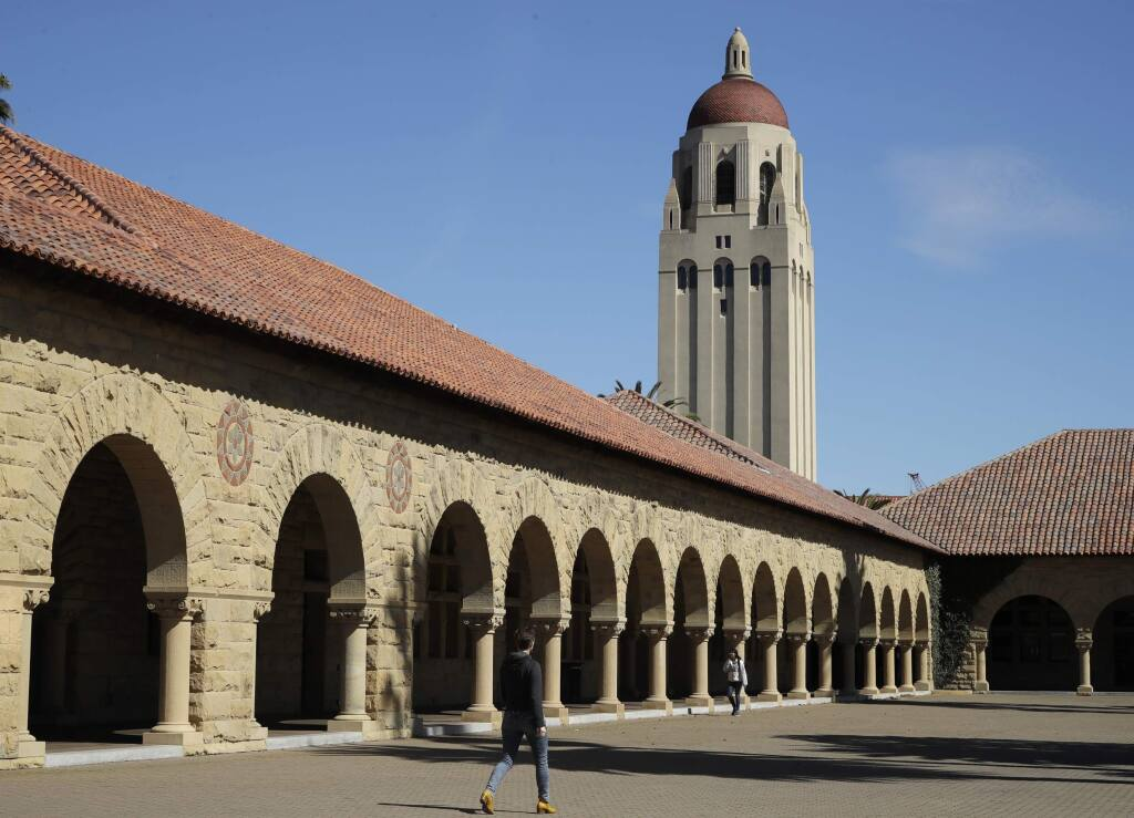 In this March 14, 2019, file photo, people walk on the Stanford University campus beneath Hoover Tower. (AP Photo/Ben Margot, File)