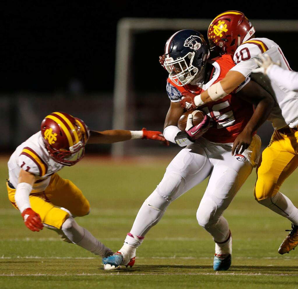 Rancho Cotate running back Rasheed Rankin (25), center, is tackled by Cardinal Newman's Zach Moran (10), right, and Jared Doolittle (11) during the first half of a varsity football game between Cardinal Newman and Rancho Cotate high schools, in Rohnert Park, California, on Friday, October 4, 2019. (Alvin Jornada / The Press Democrat)