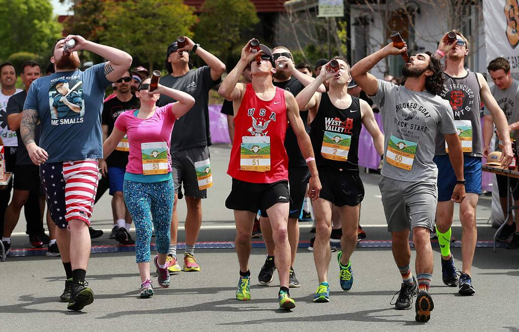 Competitors in the Beer Mile Invitational try to outrun and outdrink each other as they chugged a beer every quarter mile before dashing around The Barlow in Sebastopol on Saturday. (John Burgess/The Press Democrat)