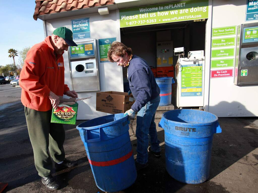 Brian Reynolds, right, helps a customer with his recyclables at rePlanet in Santa Rosa on Yulupa Avenue at Bethards Drive on March 1, 2012. (Press Democrat photo)