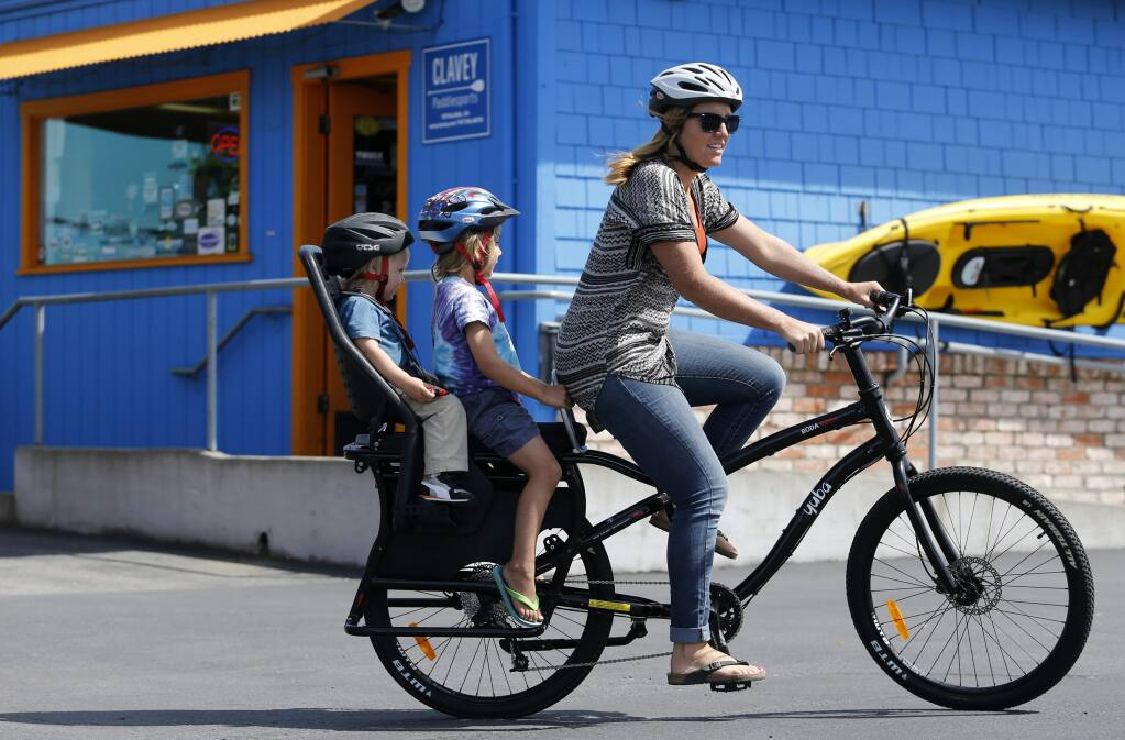 Julie Mercer-Ingram, wife of Matthew Ingram who is the Director of Marketing and Partnerships for Yuba Bicycles, rides a Boda Boda All-Terrain bicycle with her two sons Elias Ingram, 5, and Arlo, 2, in the parking lot at Yuba Bicycles on Thursday, May 19, 2016 south of Petaluma, California . (BETH SCHLANKER/ The Press Democrat)