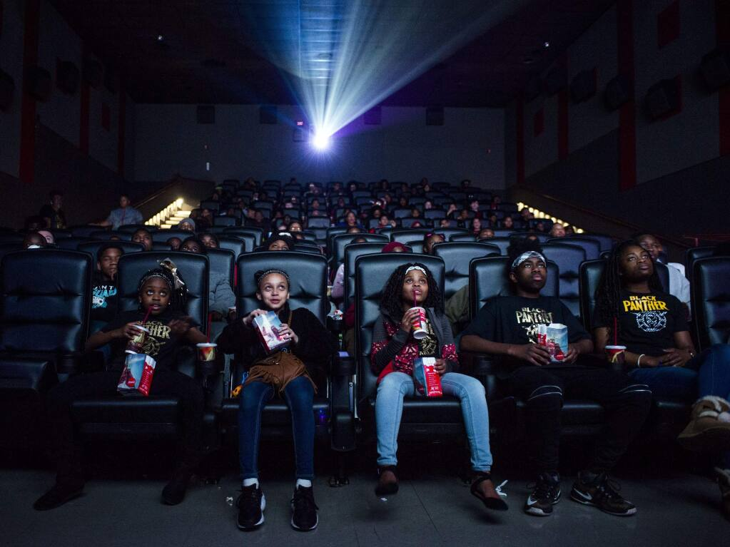 Mari Copeny, third from left, watches a free screening of the film 'Black Panther' with more than 150 children, after she raised $16,000 to provide free tickets in an entire theater on Monday, Feb. 19, 2018 in Flint Township, Mich. As 'Black Panther' debuts in theaters across the U.S., educators, philanthropist, celebrities and business owners are pulling together their resources to bring children of color to see the film that features a black superhero in a fictional, un-colonized African nation. (Jake May /The Flint Journal-MLive.com via AP)