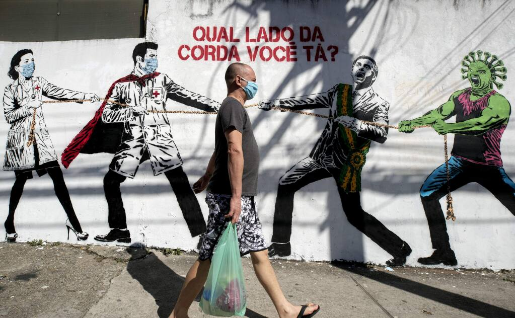 A man, wearing a protective face mask as a measure to curb the spread of the new coronavirus, walks past a mural depicting a tug-of-war between health workers and Brazil's President Jair Bolsonaro aided by a cartoon-styled coronavirus character, with a message that reads in Portuguese: 'Which side are you on?,' in Sao Paulo, Brazil, Friday, June 19, 2020. (AP Photo/Andre Penner)
