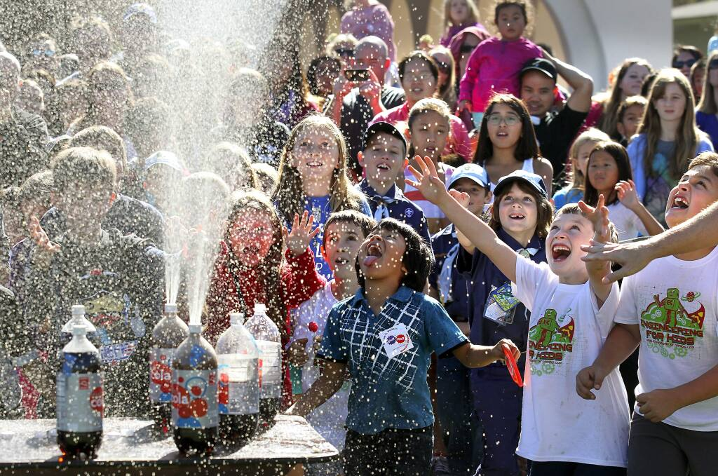 Children are sprayed with flat soda after adding Mentos at the North Bay Science Discovery Day at the Sonoma County Fairgrounds on Saturday, November 1, 2014.