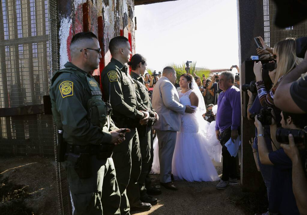 In this Nov. 18, 2017, photo, Brian Houston, of Rancho San Diego, center left, and Evelia Reyes, right, of Tijuana, Mexico, look at each other in their wedding at the 'Door of Hope,' part of the border fence between the U.S. and Mexico. A U.S. citizen, forbidden to enter Mexico, met and wed the love of his life in a brief moment when the gate separating the two countries was opened. Now it turns out the groom is a convicted drug smuggler and border agents are furious that he passed a federal background check and was approved for the 'Door of Hope.' (Howard Lipin//The San Diego Union-Tribune via AP)