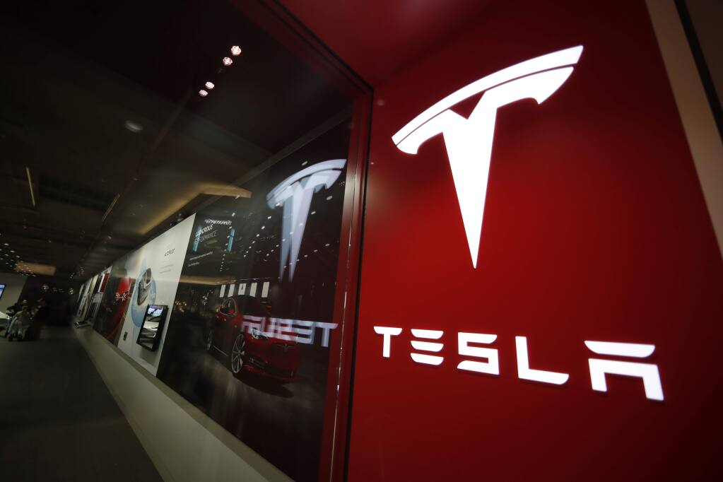 FILE- In this Feb. 9, 2019, file photo, a sign bearing the company logo is displayed outside a Tesla store in Cherry Creek Mall in Denver. (AP Photo/David Zalubowski, File)