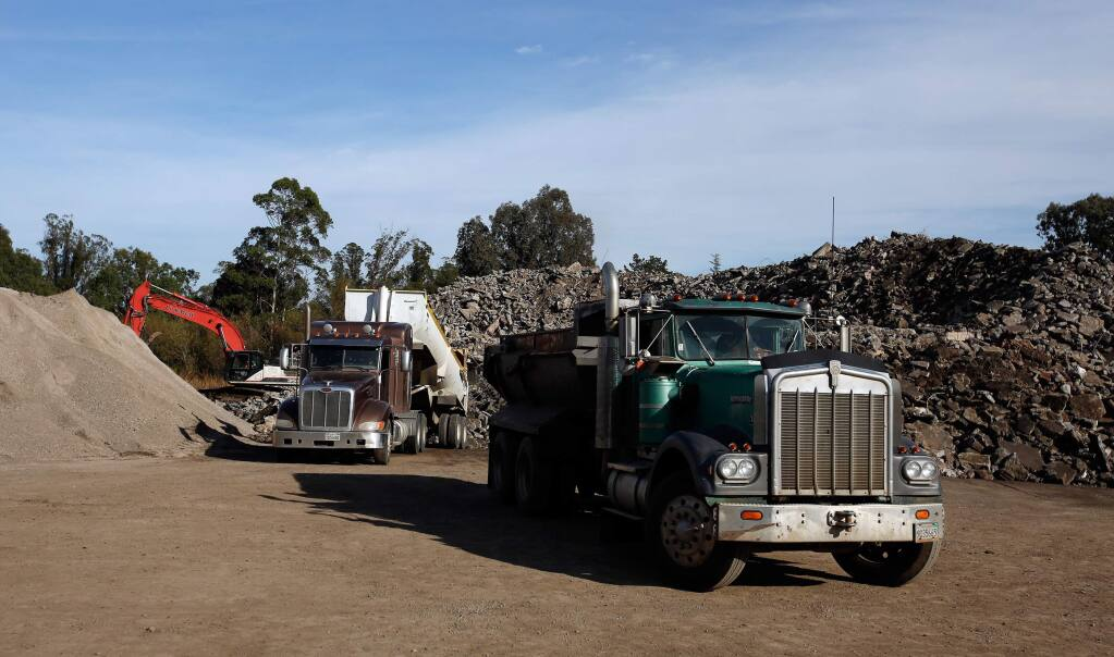A pair of dump trucks deposit loads of concrete at the Stony Point Rock Quarry in Cotati, California on Thursday, November 30, 2017. Structural concrete removed by the Army Corps of Engineers from sites destroyed by the wildfires are brought to Stony Point Rock Quarry for recycling. (Alvin Jornada / The Press Democrat)