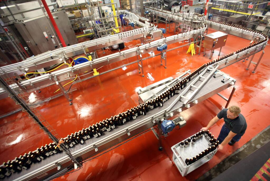 Ross Campbell, laboratory tech for quality assurance moves bottles of beer onto the line at the Lagunitas Brewing Co., production facility in Petaluma, Friday, October 24, 2014. (Crista Jeremiason / The Press Democrat)