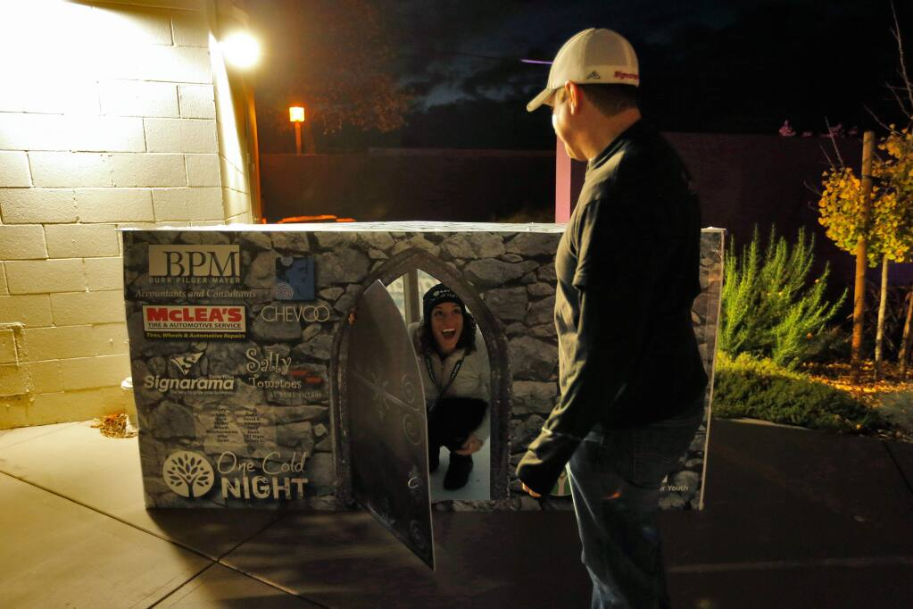 Social Advocates for Youth Cat Cvengros, left, tries out a cardboard box made by participant Aaron Friedman, right, owner of Sign-a-rama, featuring logos of businesses that sponsored him for Social Advocates for Youth's One Cold Night event at the SAY Dreamcenter in Santa Rosa, California on Friday, November 18, 2016. (Alvin Jornada / The Press Democrat)
