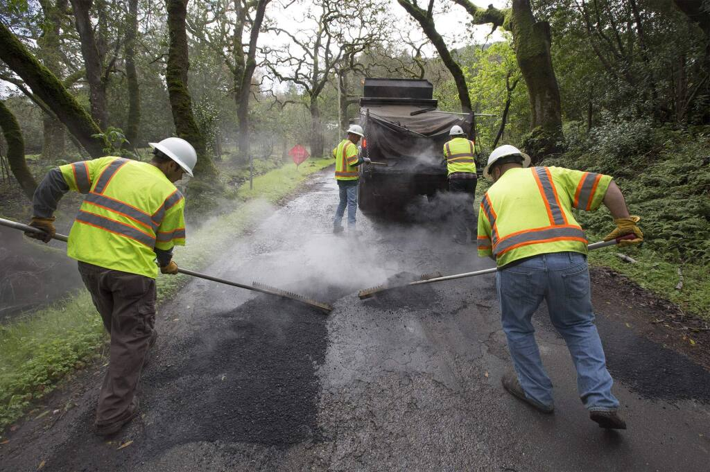 A county crew fills potholes on Enterprise Road on Monday, March 6, 2017. (Photo by Robbi Pengelly/Index-Tribune)