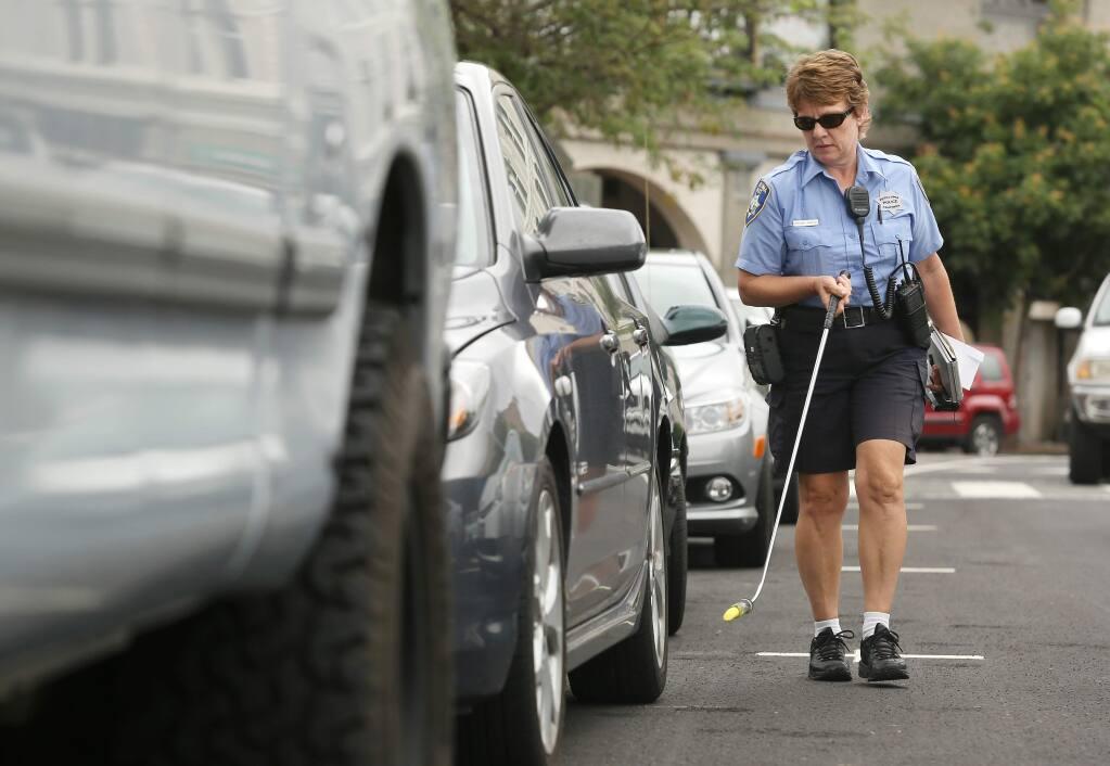 Petaluma Parking Enforcement Officer Charlene Lavezzoli marks parked cars with chalk in downtown Petaluma on Wednesday, June 26, 2013. (Conner Jay/The Press Democrat)