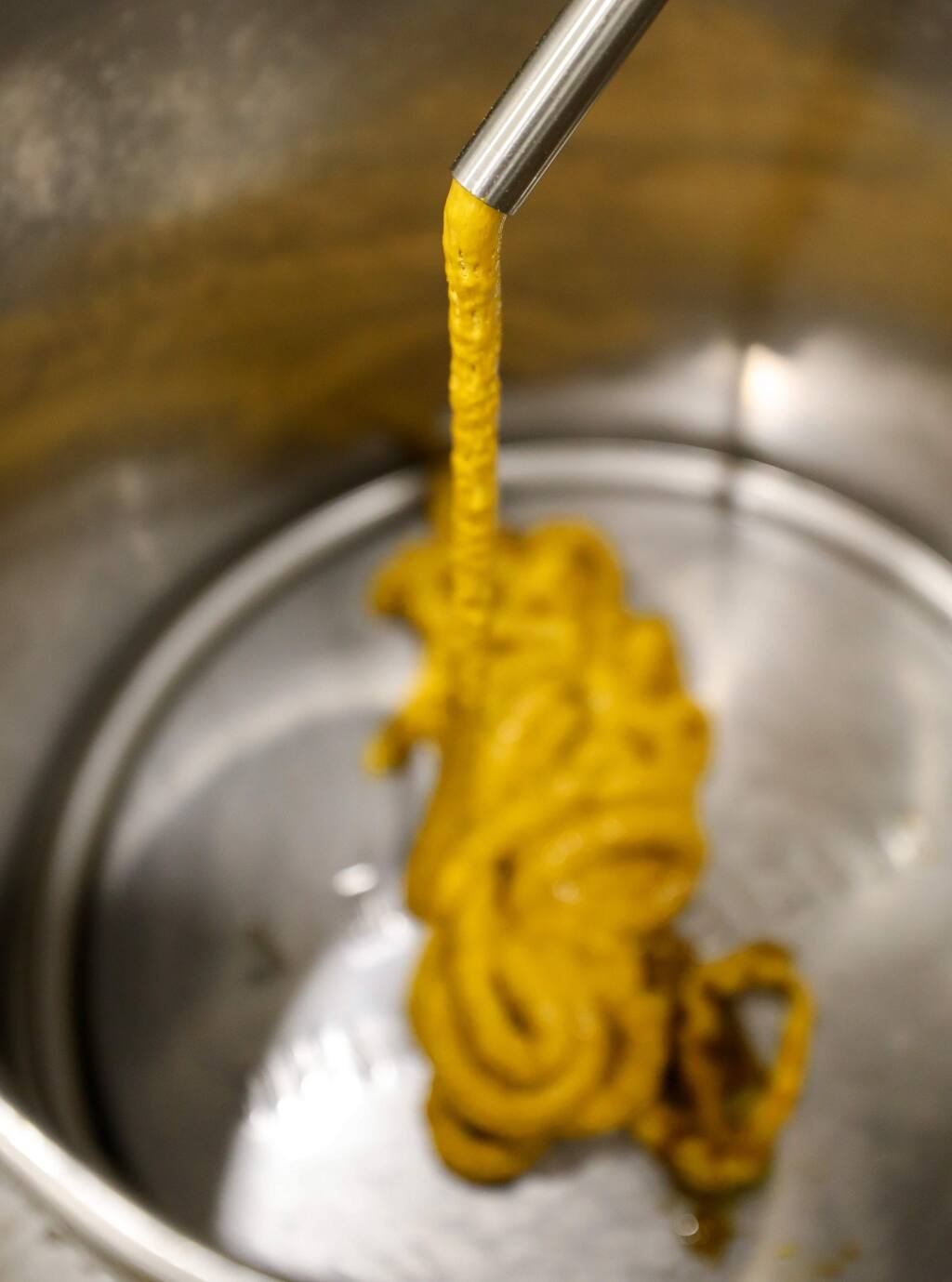Cannabis extract slowly exits an extraction machine, before it is subjected to additional layers of refinement, at the SPARC production facility, in Santa Rosa on Friday, February 14, 2020. (Christopher Chung/ The Press Democrat)