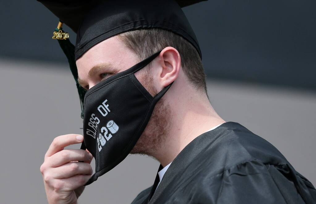 Roman Hutchison adjusts his mask while participating in the drive-thru commencement ceremony at Maria Carrillo High School, in Santa Rosa on Friday, May 29, 2020. (Christopher Chung/ The Press Democrat)