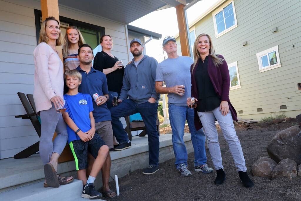Hidden Valley neighborhood residents Beth Cuniberti, left, Carlo Cuniberti, 10, Lily Cuniberti, 13, Dan Cuniberti, Erica Todhunter, Matt Todhunter, Rich Peters and Tracy Condron were all friends before the Tubbs fire, getting together for block parties on Flintwood Drive in Santa Rosa. The experience of the fire and subsequent rebuilding of their homes have brought them closer together.(Christopher Chung/ The Press Democrat)