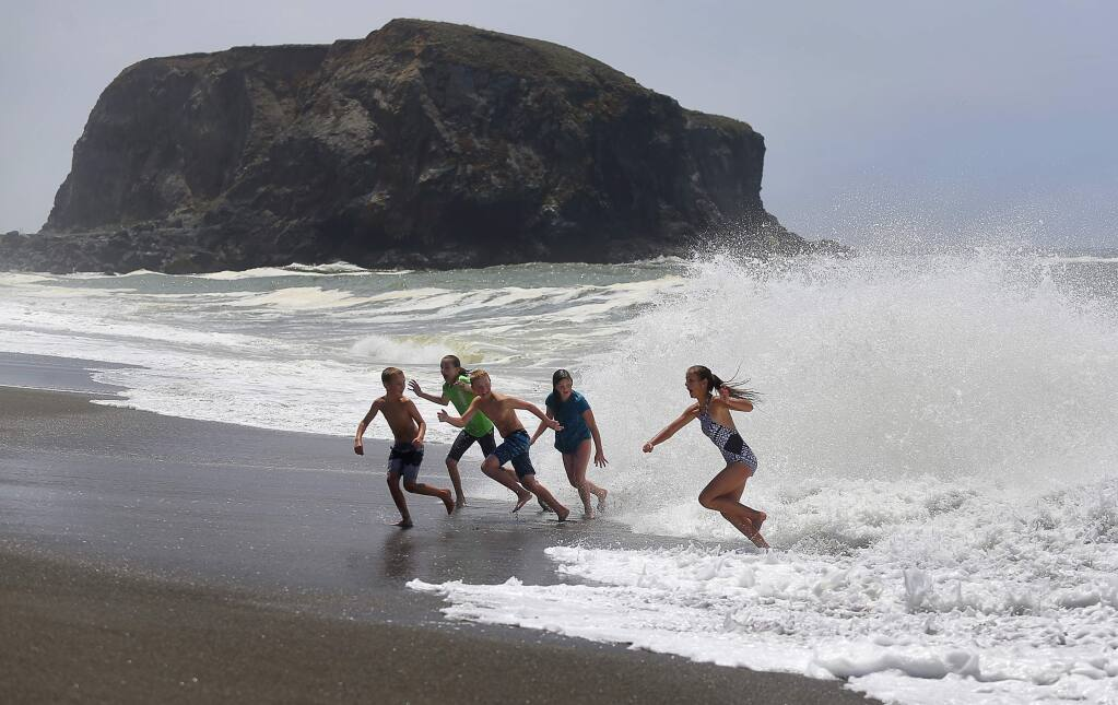 Russell Reed, left, Kate Hatch, Max Reed, Maggie Hatch, and Annabelle Reed, run away from a wave at Goat Rock Beach, south of Jenner on Friday, July 28, 2017. The children, visiting from Cedar Hills, Utah, were later warned of the dangerous surf by a California State Parks lifeguard.(Christopher Chung/ The Press Democrat)