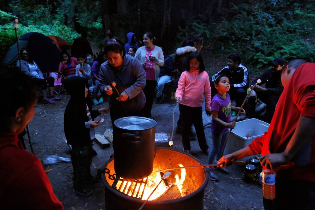 Children and adults roast marshmallows around a fire and sing songs in Spanish during a Latino Outdoors camp out at the Pomo Canyon Environmental Campground near Duncans Mills on Saturday, September 5, 2015. (Alvin Jornada / The Press Democrat)