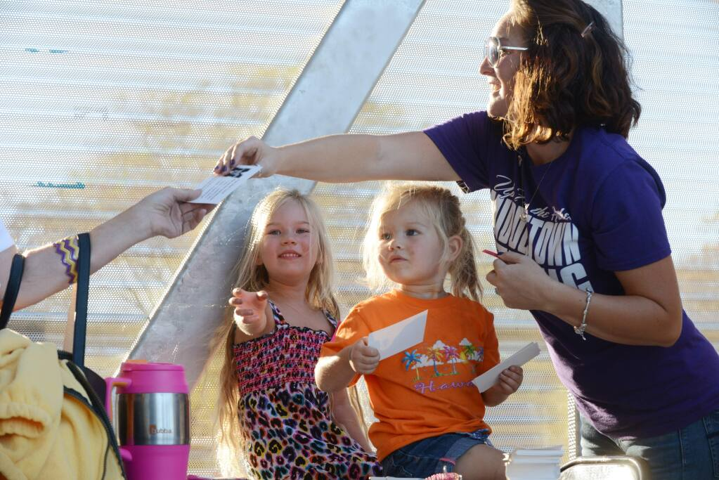 Erika Galvan of Middletown, far right, greets attendees with her daughters Camila, 2 (center) and Trinity, 4, before the start of the Middletown High School football team's first home game since the recent catastrophic Valley fire. The Galvan family lost their home in the recent fire and are currently living on their property in a trailer they recently purchased. (Erik Castro/for The Press Democrat)