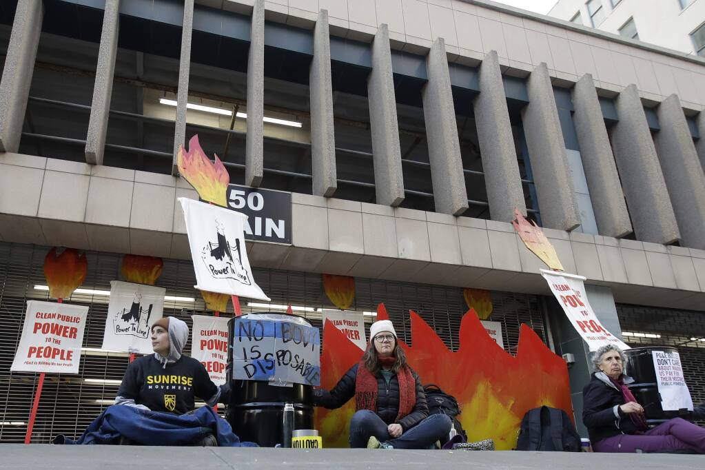 Protesters sit outside of an entrance to a Pacific Gas & Electric building in San Francisco, Monday, Dec. 16, 2019. Pacific Gas and Electric will have to quickly reshuffle its board of directors and redraw a complex plan addressing more than $50 billion in potential wildfire claims to gain Gov. Gavin Newsom's support in time to meet a fast-approaching deadline to emerge from bankruptcy protection. (AP Photo/Jeff Chiu)