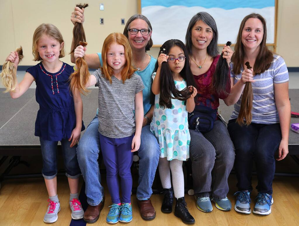 Ellie Bugarske, left, Hazel Bugarske, Marci Cook, Camila Vazquez, Joanna Huie and Charity Higareda hold up the hair that they had cut off to donate to Wigs for Kids, at Mattie Washburn Elementary School in Windsor, on Thursday, February 25, 2016. (Christopher Chung/ The Press Democrat)