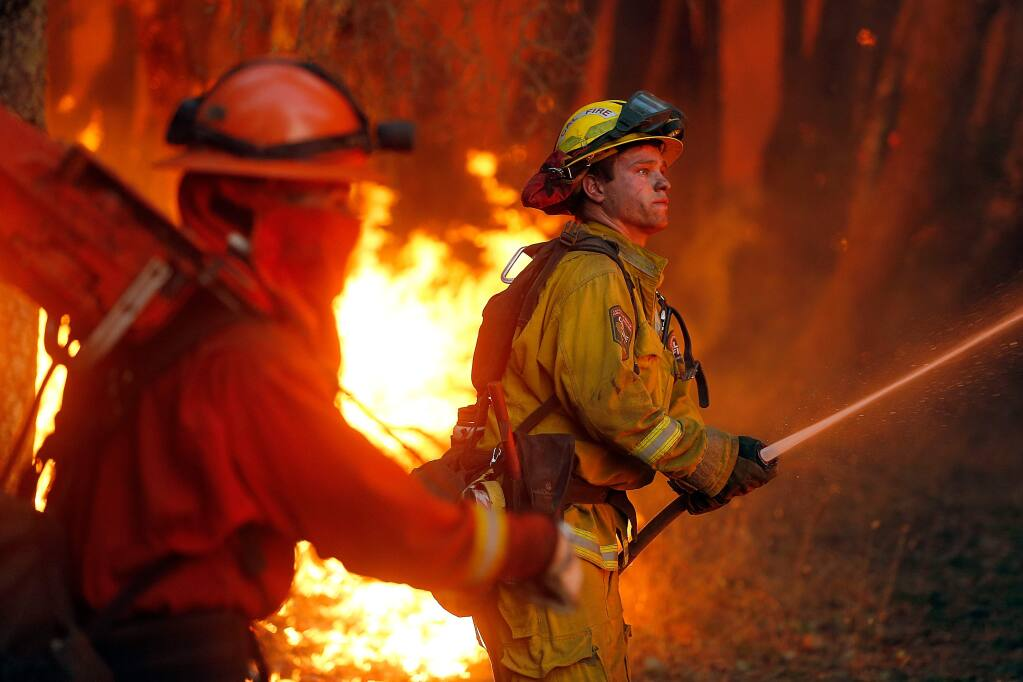 Cal Fire Siskyou firefighter Chance Jackson, right, cools down some burning vegetation during a firing operation at the Oakmont fire in Santa Rosa, California on Tuesday, October 17, 2017. (Alvin Jornada / The Press Democrat)