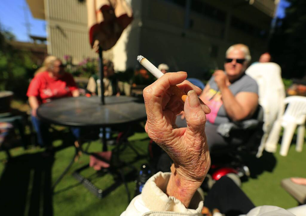 Smokers who live in the Bethlehem Towers in Santa Rosa light up outside in a designated smoking area in 2015. (JOHN BURGESS/ PD)