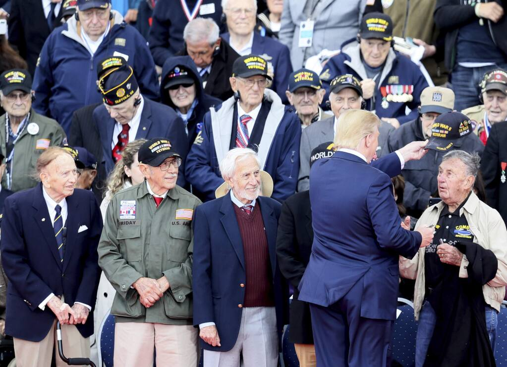 U.S. President Donald Trump greets World War II veterans during a ceremony to mark the 75th anniversary of D-Day at the Normandy American Cemetery in Colleville-sur-Mer, Normandy, France, Thursday, June 6, 2019. World leaders are gathered Thursday in France to mark the 75th anniversary of the D-Day landings. (AP Photo/David Vincent)