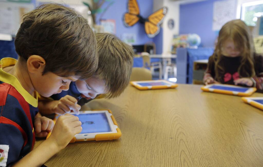 Tablets are portals to a million possibilities. But some teachers are asking if the benefits offset the cost. (STEPHAN SAVOIA / Associated Press)