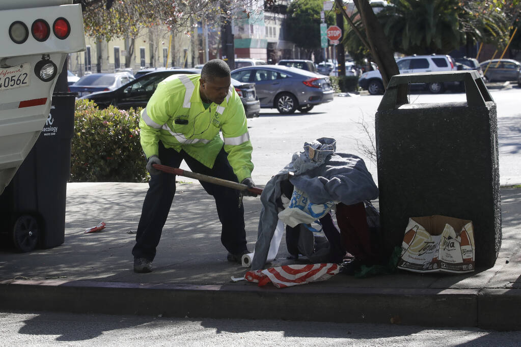 A Recology San Francisco worker picks up clothing and bags next to a trash can in San Francisco, Tuesday, Feb. 18, 2020. (AP Photo/Jeff Chiu)