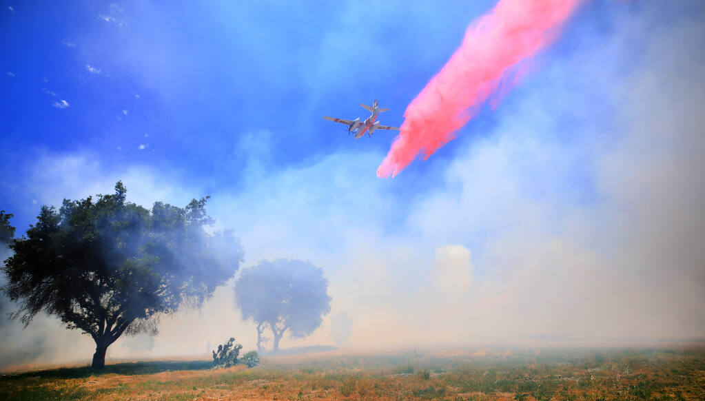 A Cal Fire air tanker drops fire retardant across the head of the west fire on Mark West Springs Road, Wednesday, May 26, 2021 near Larkfield. (Kent Porter / The Press Democrat) 2021