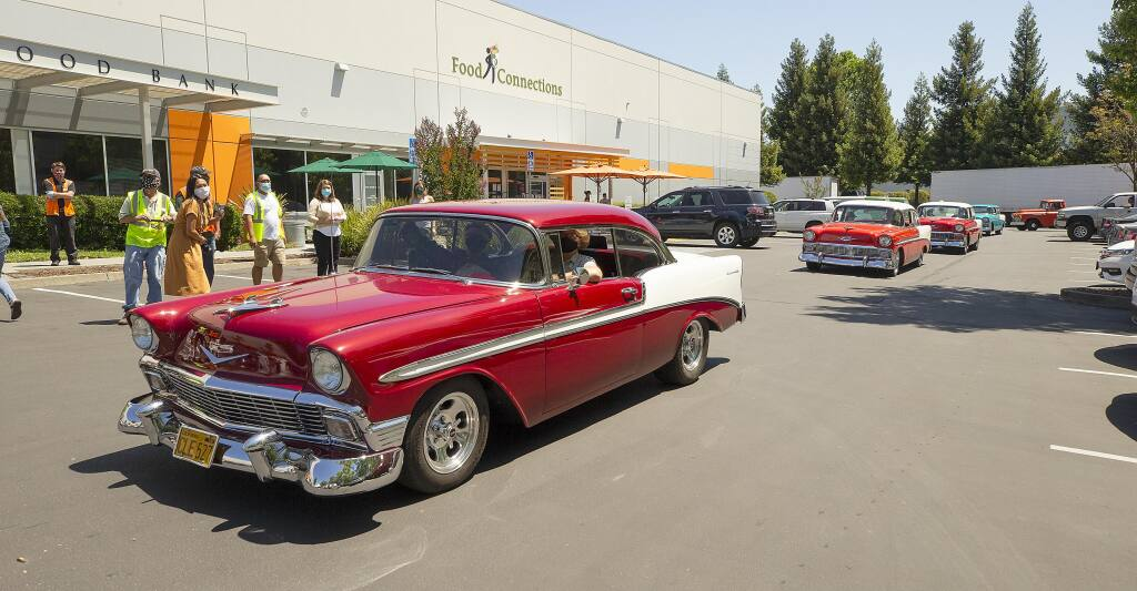 The Redwood Empire Classic Chevy Club presented a check for $1,500 to the Redwood Empire Food Bank and then entertained volunteers with a classic car parade on Wednesday, July 1, 2020. (Photo by John Burgess / The Press Democrat).
