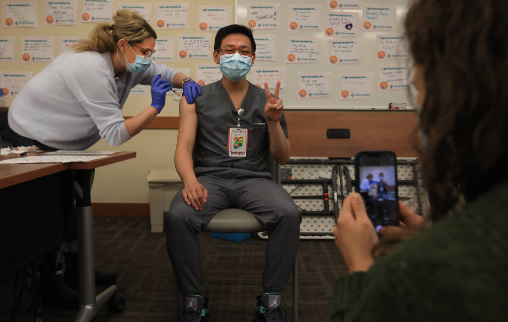 Sutter doctor Jimmy Le is photographed by fellow doctor Hannah Kazak as they receive their second round of the Pfizer-BioNTech COVID-19 vaccine at Sutter Santa Rosa Regional Hospital, Friday, Jan. 8, 2021. (Kent Porter / The Press Democrat) 2021