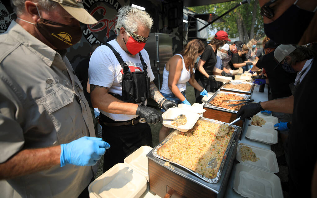 Guy Fieri plates food he and his employees cooked as volunteers put together meals for those working to contain the LNU Lightning Complex fires, Friday, Aug. 28, 2020, at the Calistoga Fairgrounds. (Kent Porter / The Press Democrat) 2020