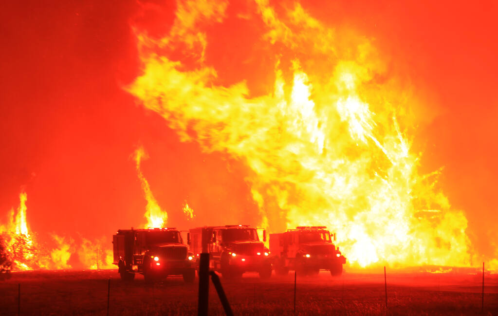 Firefighters took refuge in their trucks in a cleared field as the Hennessey fire jumped Knoxville Berryessa Road, Tuesday, Aug. 18, 202. (Kent Porter / The Press Democrat) 2020
