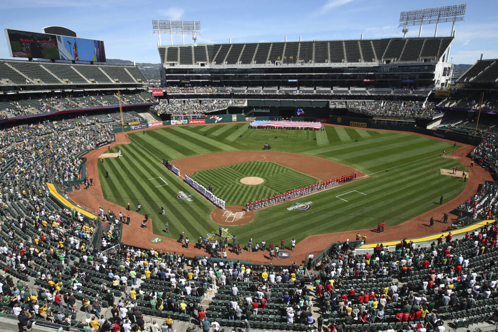 The Los Angeles Angels and Oakland Athletics stand for the national anthem at the Oakland Coliseum on opening day in 2018. (Ben Margot / ASSOCIATED PRESS)