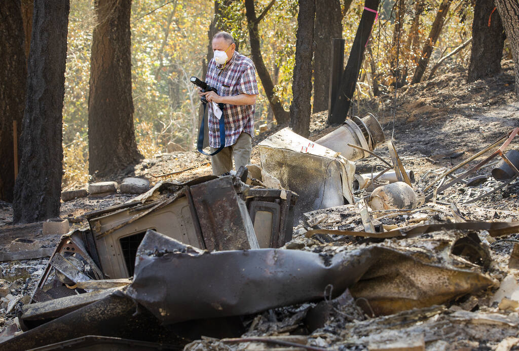 Jay Gamel, longtime publisher and editor of the Kenwood Press photographs the remains of a house he owned for nearly 50 years on Adobe Canyon Road when the Glass fire raged through the area near Sugarloaf State park.  (John Burgess / The Press Democrat)