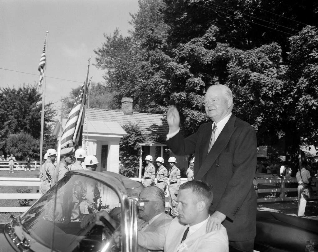 Former President Herbert Hoover, riding in a West Branch, Iowa parade marking his 80th birtday, waves as he passes the little white house where he was born. (WILLIAM P. STRAETER / Associated Press, 1954)