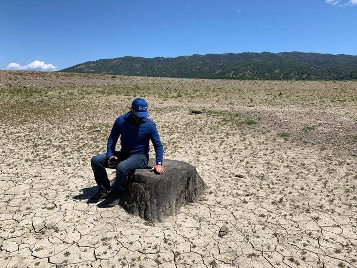 Sonoma Water's Brad Sherwood sits on a stump in a parched Lake Mendocino. Photo courtesty Brad Sherwood.