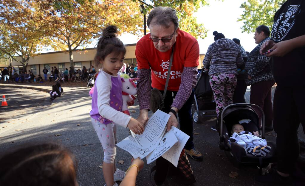 Francois Piccin lost his home during the Tubbs fire, has also volunteered his time helping those in Paradise and Camp fire victims and is now volunteering at the Healdsburg Kincade fire recovery center, Tuesday Nov. 5, 2019. Piccin gives out crayons and coloring pages to Jessica Weisheitinger's two children Cali and Tori Swan.(Kent Porter / The Press Democrat) 2019