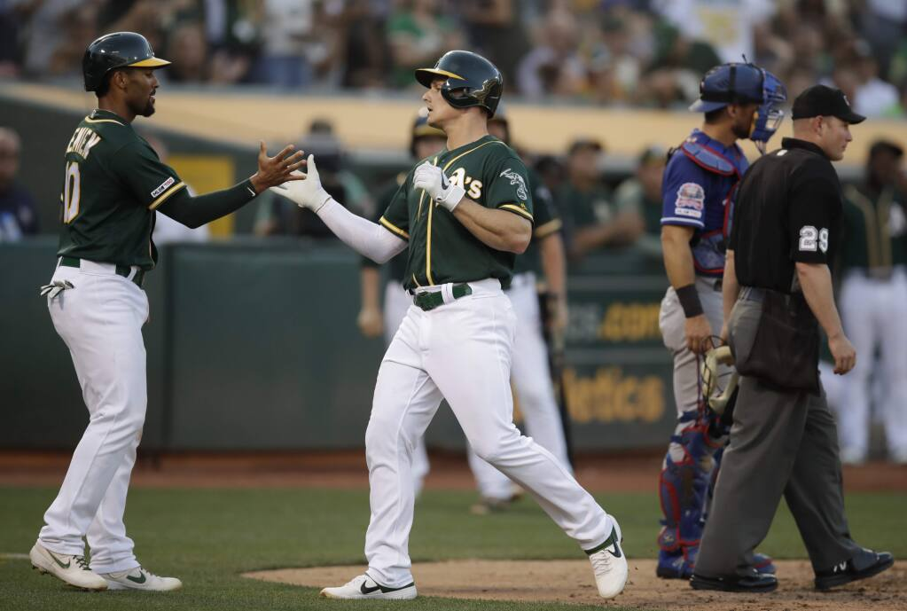 The Oakland Athletics' Matt Chapman, center, celebrates with Marcus Semien, left, after hitting a two-run home run off the Texas Rangers' Adrian Sampson in the fifth inning, Saturday, July 27, 2019, in Oakland. (AP Photo/Ben Margot)