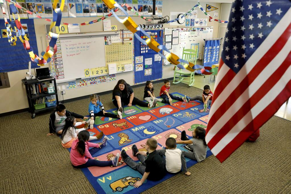 Kindergarten teacher Jaime Wanke leads a class of only 13 students, out of her usual 22, in stretches at Roseland Creek Elementary School in Santa Rosa, Thursday, Feb. 16, 2017. About 40 percent of the school's student body was absent Thursday.(BETH SCHLANKER/ The Press Democrat)