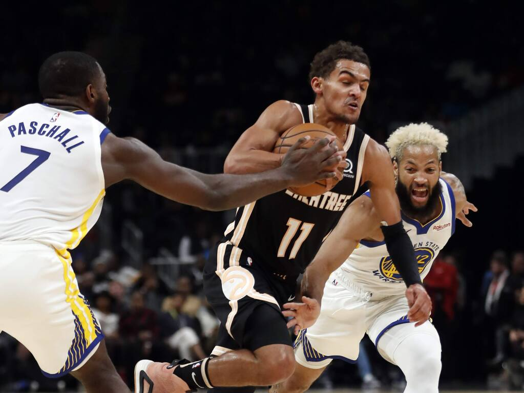 Atlanta Hawks guard Trae Young (11) drives between Golden State Warriors' Eric Paschall (7) and Ky Bowman (12) in the first half of an NBA basketball game Monday, Dec. 2, 2019, in Atlanta. (AP Photo/John Bazemore)