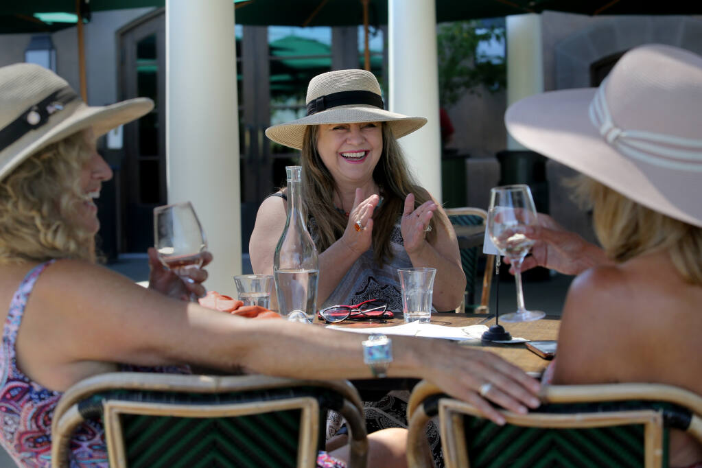 Friends Peggy Koorhan, from left, Sandra Hanns, and Alta Ridley drink wine at Francis Ford Coppola Winery in Geyserville, Calif., on Thursday, June 24, 2021.(Beth Schlanker/The Press Democrat)