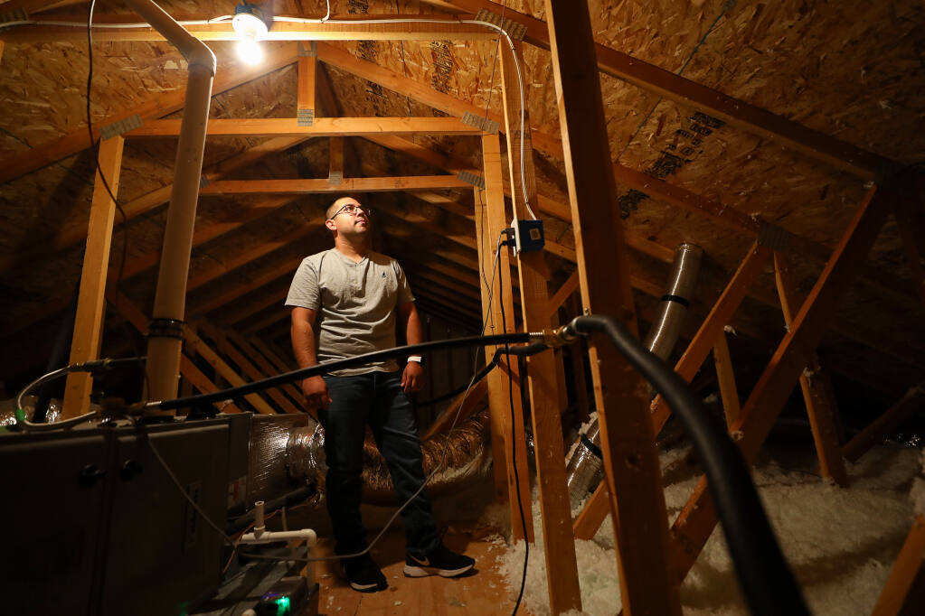 Miguel Hernandez and his family have been living in their rebuilt Coffey Park area home under a temporary occupancy permit for the past  2½ years.  The contractor that built the home failed to install radiant barriers and adequate insulation in the attic. (Christopher Chung/ The Press Democrat)