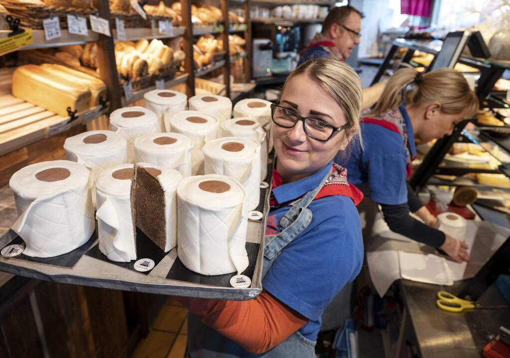 A saleswoman of the bakery Schuerener Backparadies shows a tray with round marble cakes wrapped in fondant that look like toilet paper rolls in Dortmund, Germany, Wednesday, March 25, 2020. The toilet paper cake has become a 'bestseller' during the Corona crisis. (Bernd Thissen/dpa via AP)