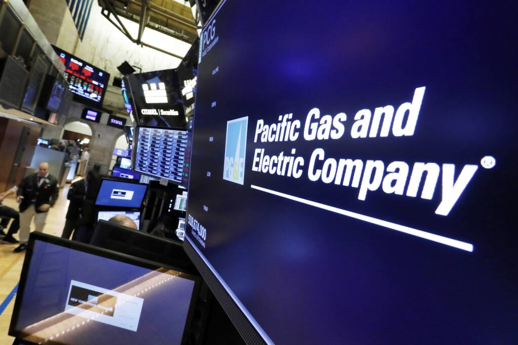 FILE - This Jan. 14, 2019, file photo shows the logo for Pacific Gas & Electric Co. above a trading post on the floor of the New York Stock Exchange. (AP Photo/Richard Drew, File)